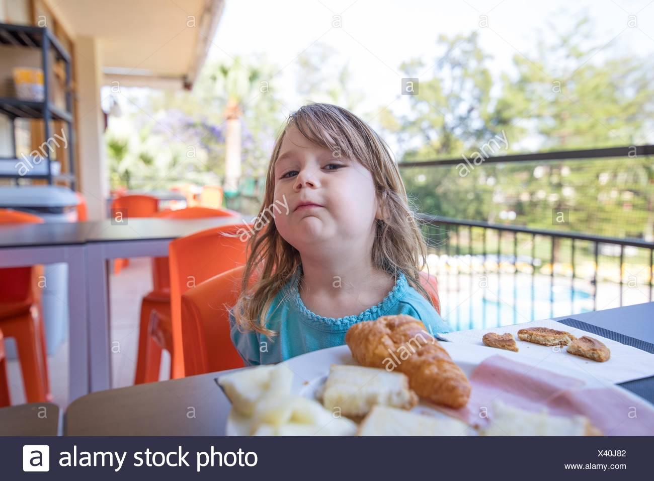Portrait von Blond kaukasier Kind drei Jahre alt mit blauen Shirt, beim Frühstück, auf der Suche mit herausfordernden lustiges Gesicht, mit Essen auf Teller, im Sitzen Stockbild