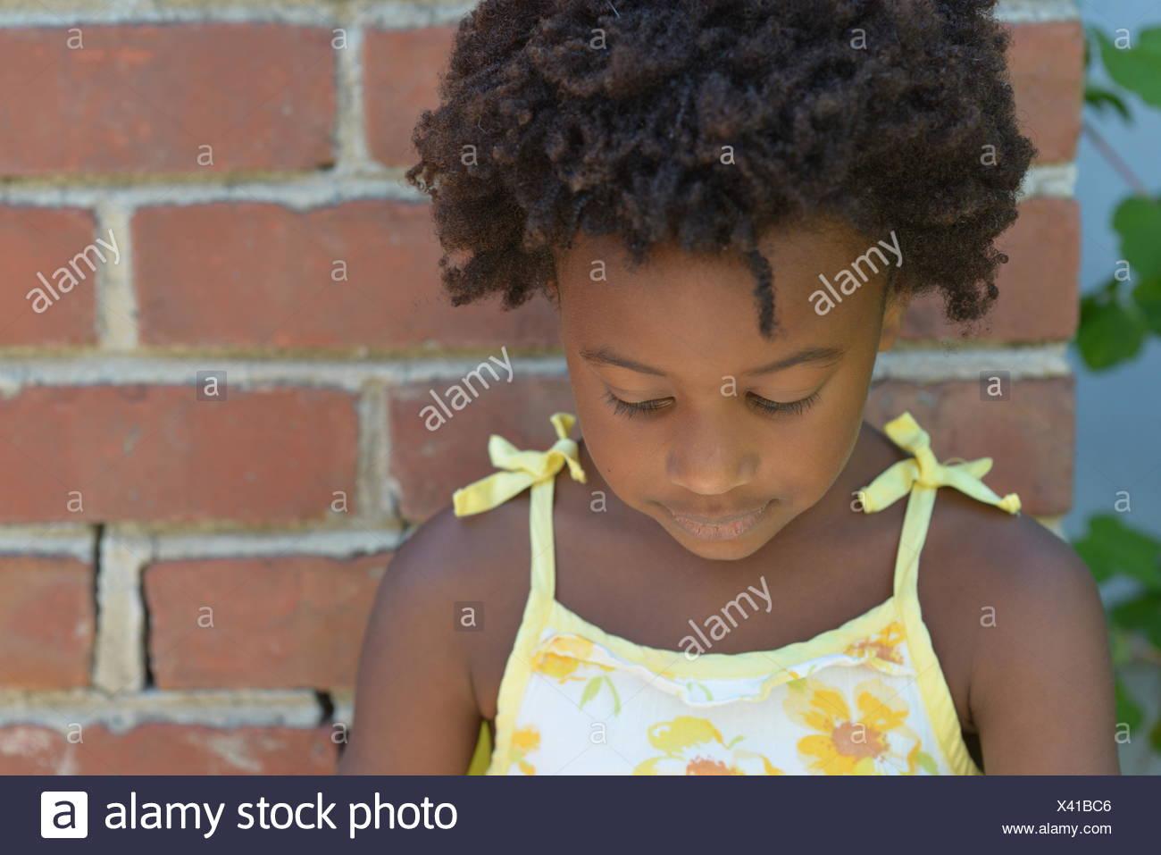 Mädchen, die durch eine Mauer nach unten stehend Stockbild