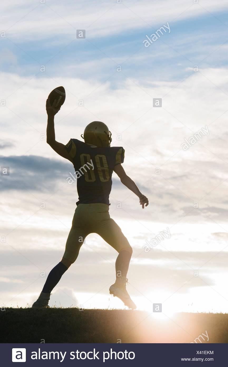 Junge american Footballspieler rund um den Ball zu werfen Stockbild