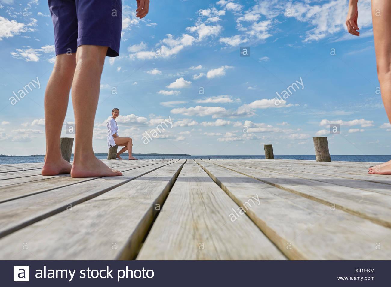 Junge Frau sitzt auf Post auf hölzernen Pier, Blick auf Freunde stehen weitere entfernt Stockbild