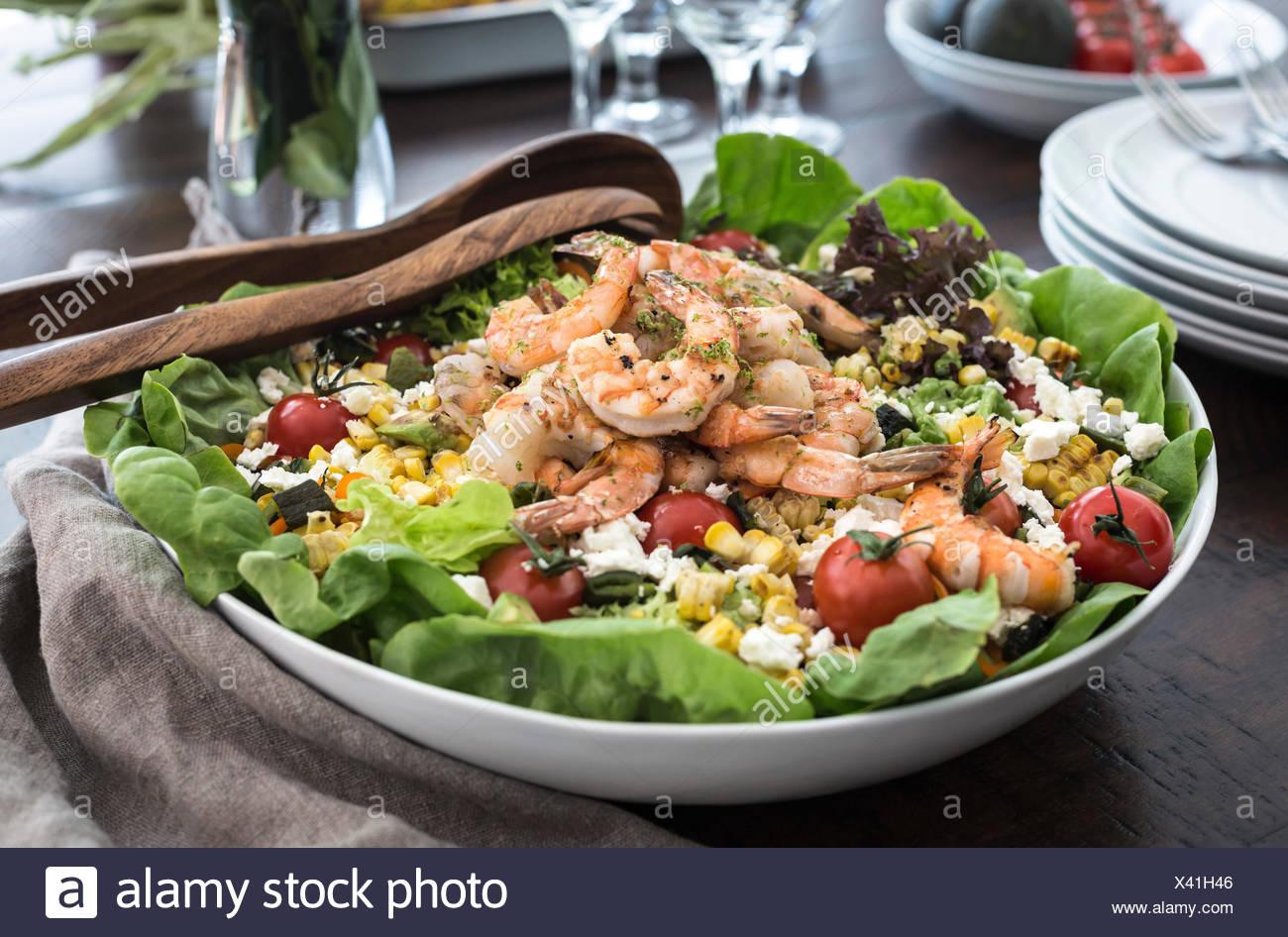 Eine große Schale mit gegrillten Shrimps und Feldsalat wird aus der Vorderansicht fotografiert. Stockbild