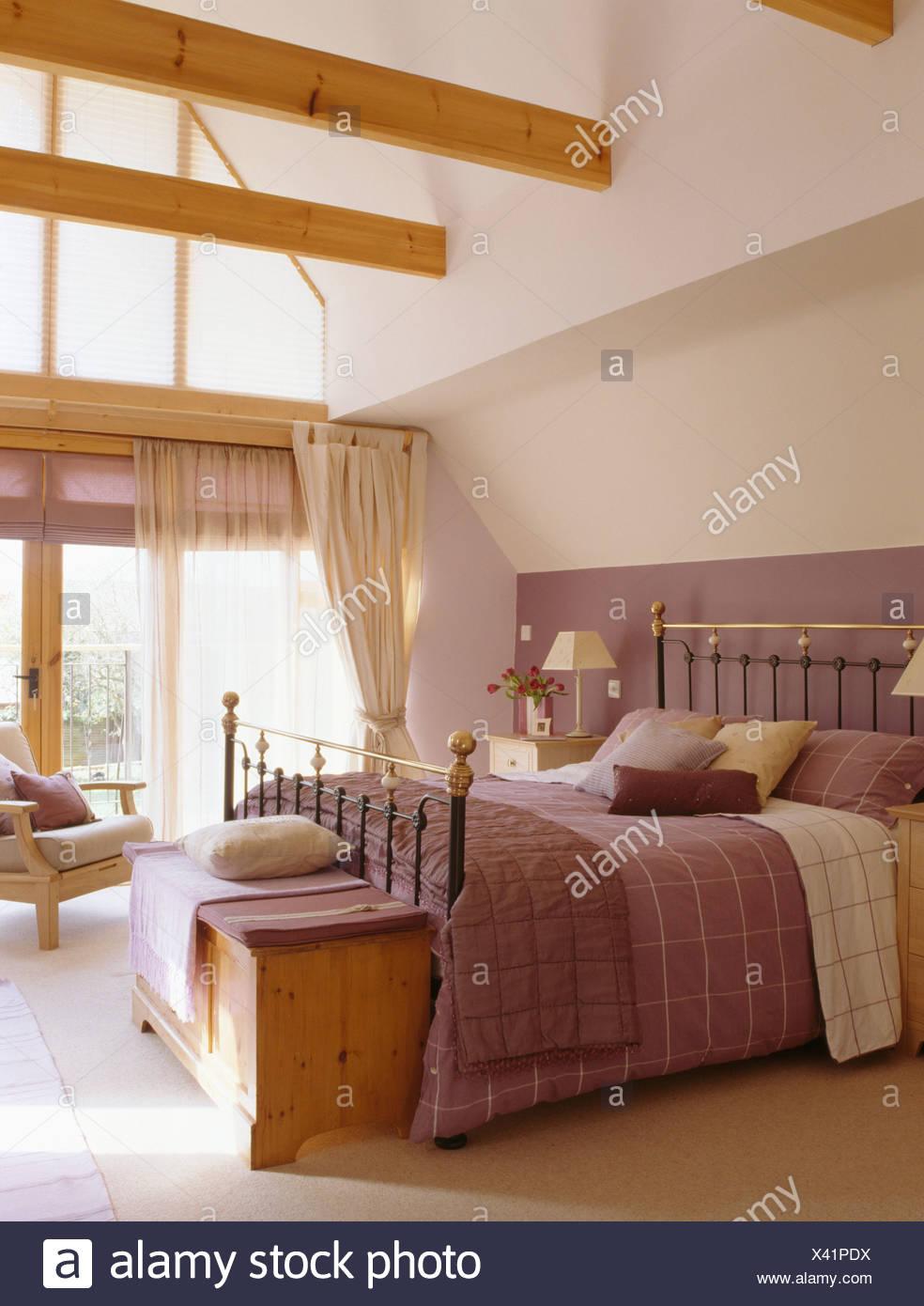 Holzkiste unter Antik Messingbett mit lila Bettwäsche in großen ...