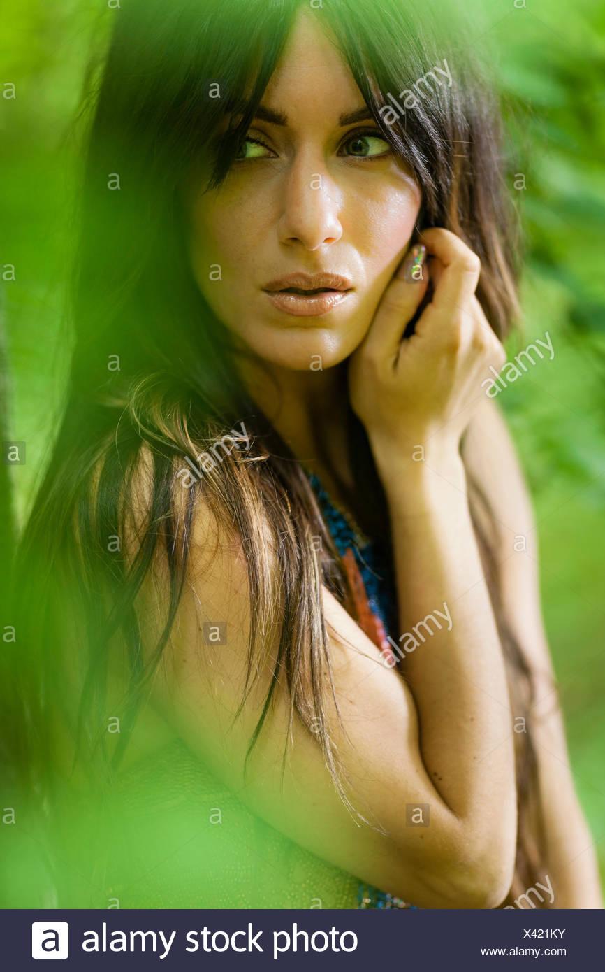 Eine Frau mit langen braunen Haaren draußen im Wald. Stockbild