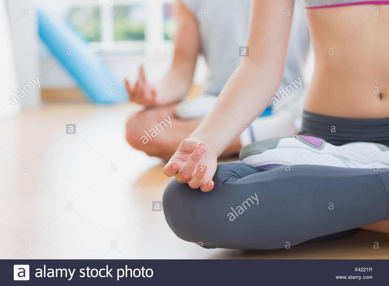 Sportliches Paar in Meditation stellen im Fitness-studio Stockbild