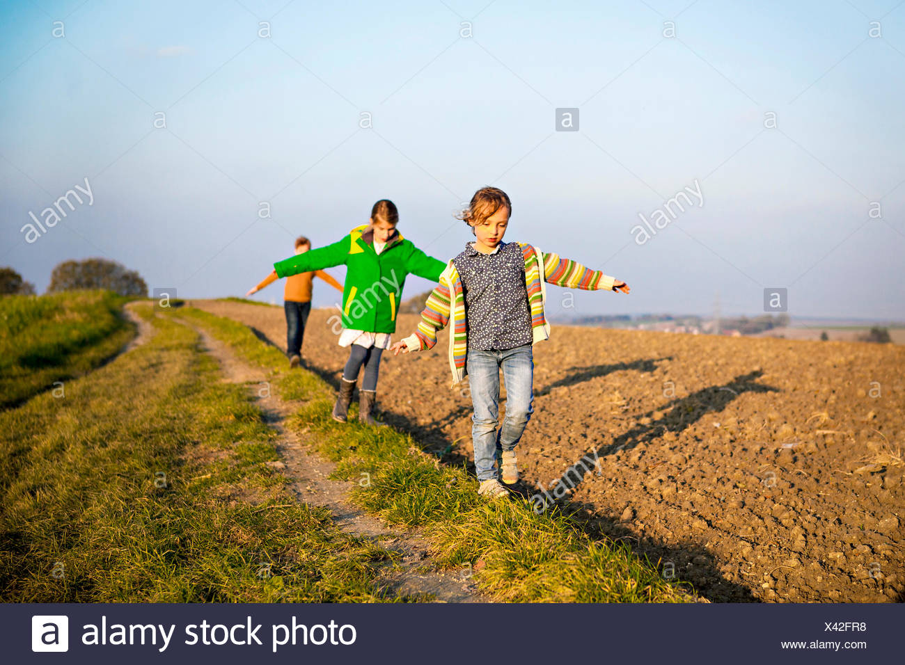 Drei Kinder spielen im freien Stockbild