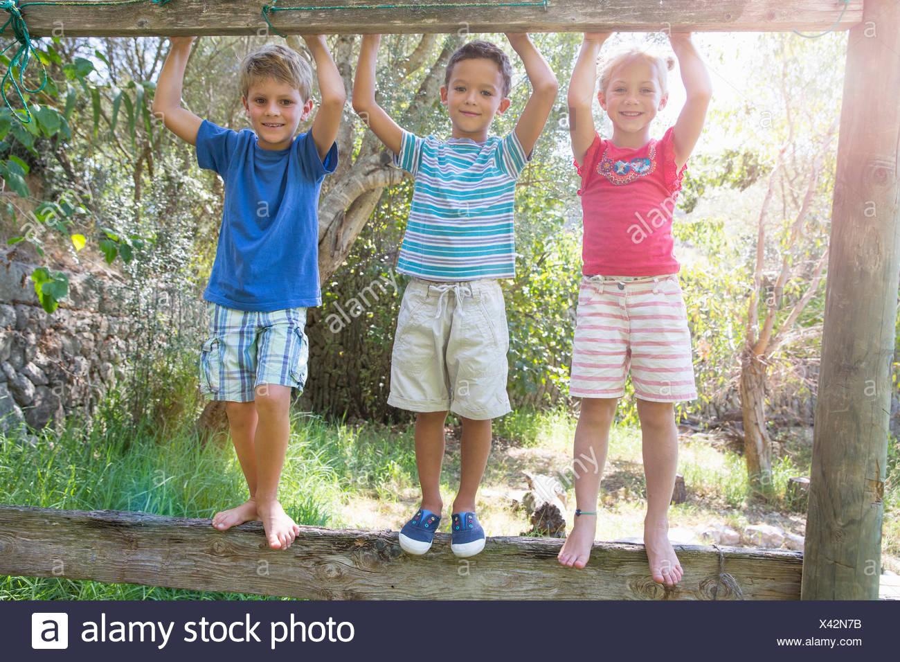 Drei Kinder im Garten stehen am Zaun Stockbild