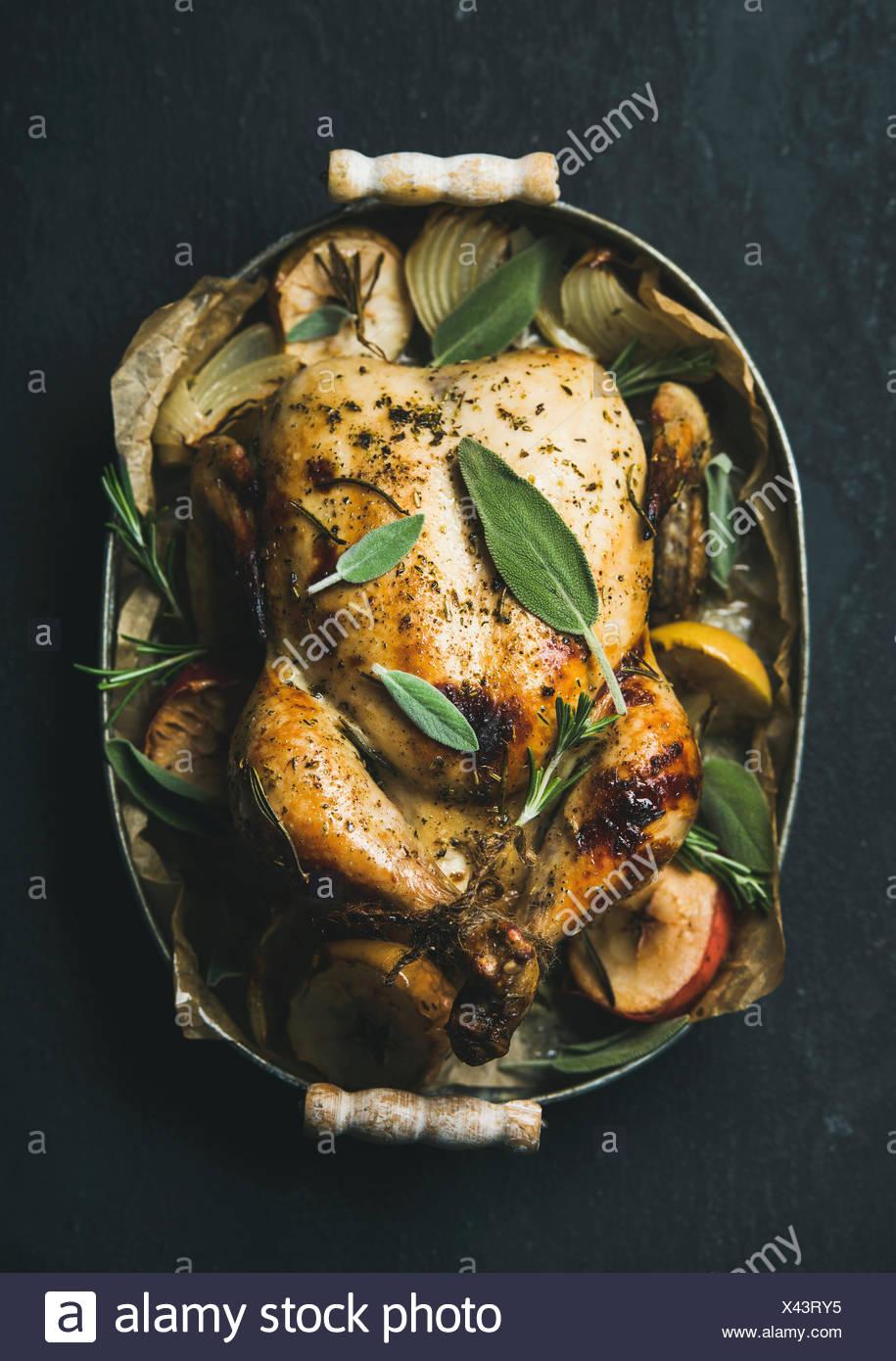 Ofen gebratenes ganzes Huhn mit Zwiebeln, Äpfel und Salbei in Metall Tablett über dunklem Stein, Ansicht von oben. Stockbild