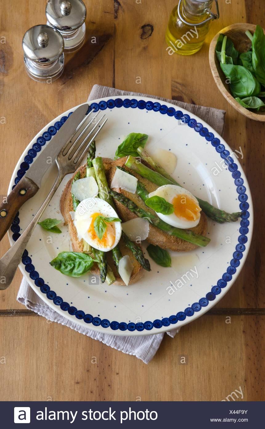 Weich gekochte Eier, Spargel und Pecorino auf Toast. Stockbild
