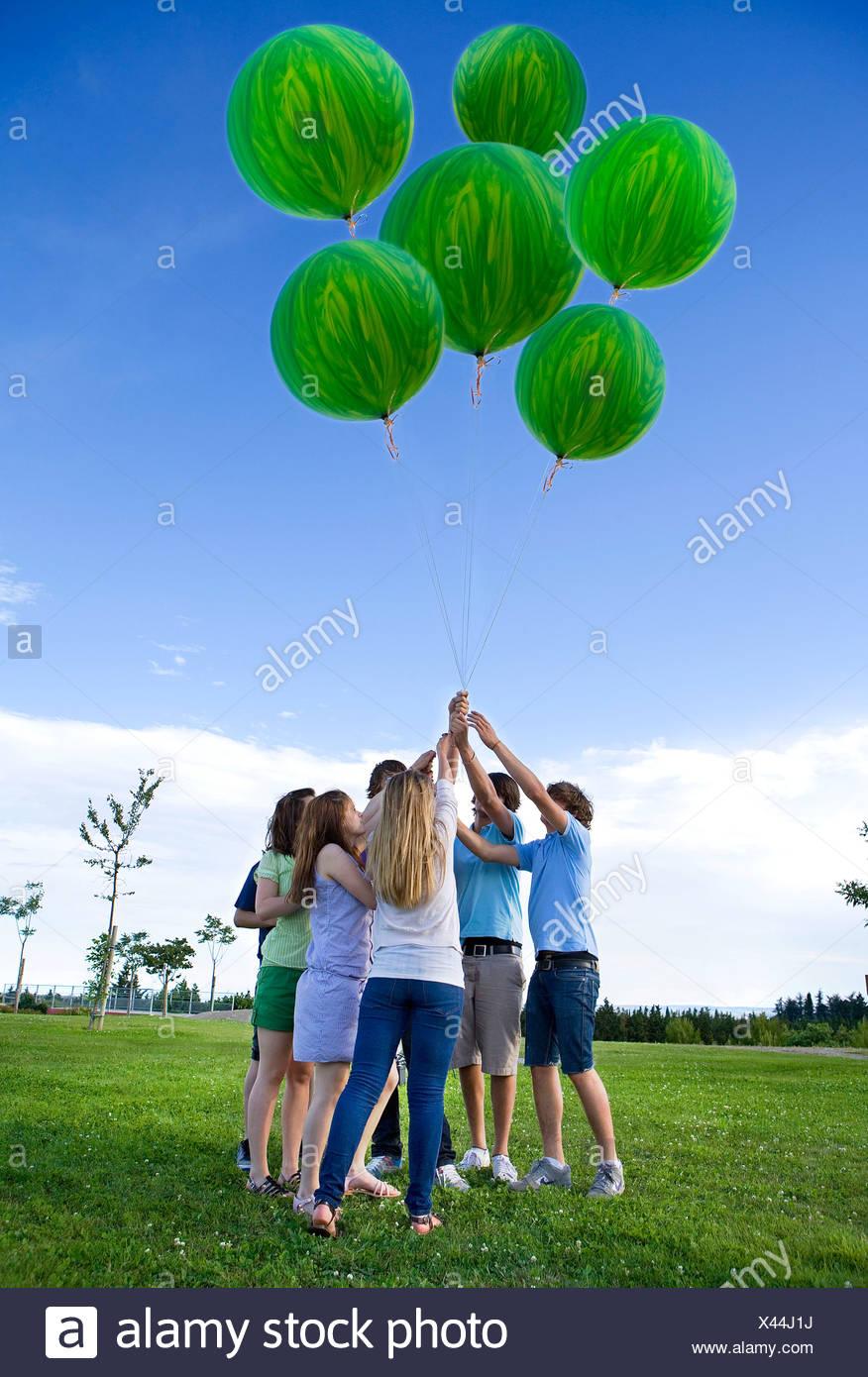 Jugendliche, die mit Helium grün Ballons Stockbild