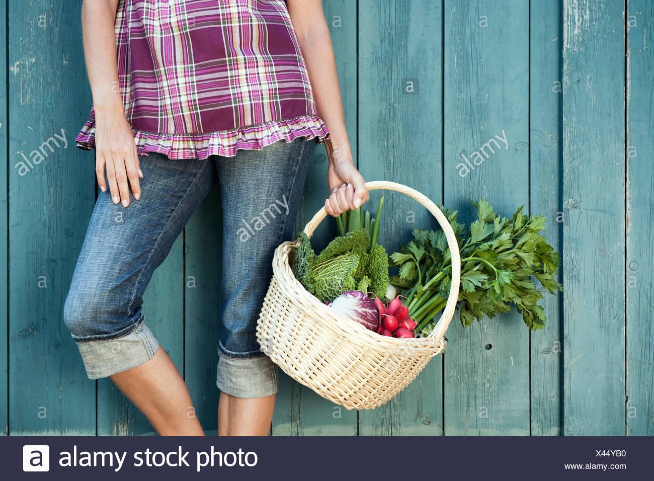 Deutschland, Bayern, Frau lehnte sich gegen Scheunentor hält Korb mit frischem Gemüse Stockbild