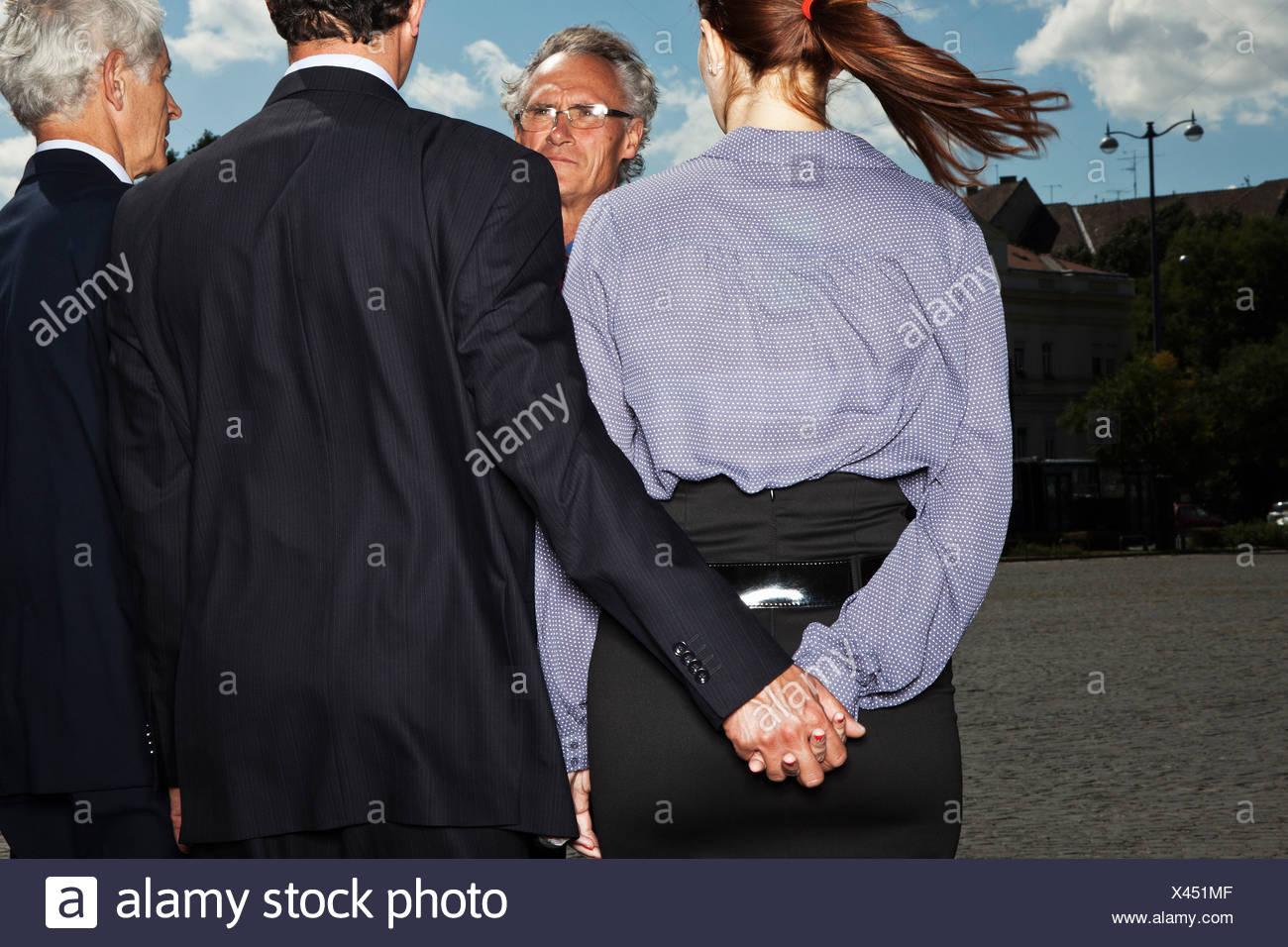Geschäftsleute, die heimlich Hand in Hand Stockbild
