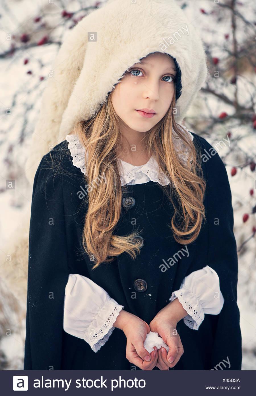 Traurig aussehende Mädchen halten Schnee in der Form eines Herzens Stockbild