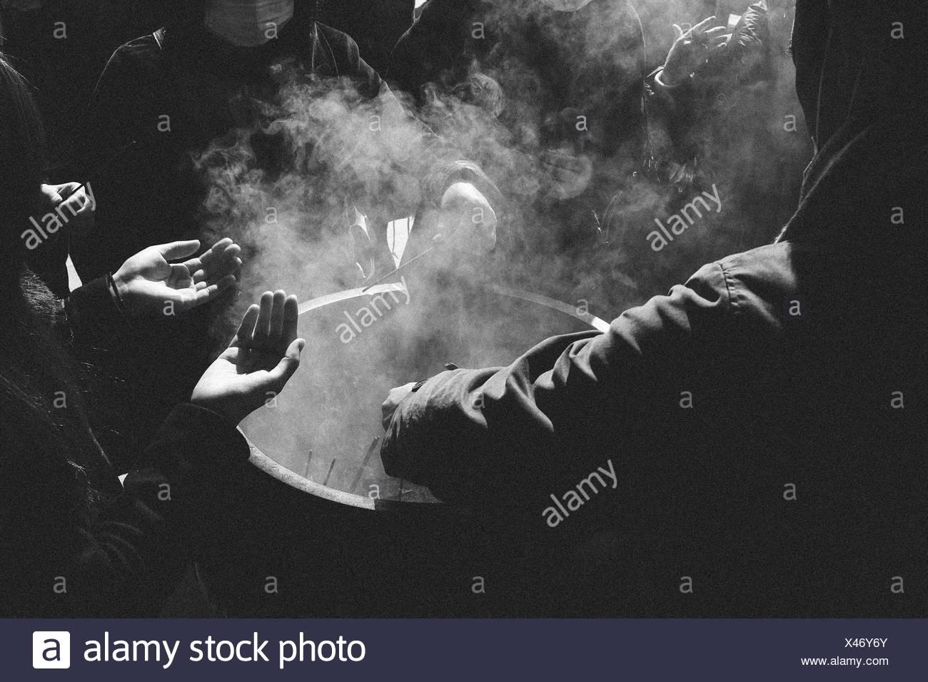 Gruppe von Menschen rund um Rauch Container Stockbild