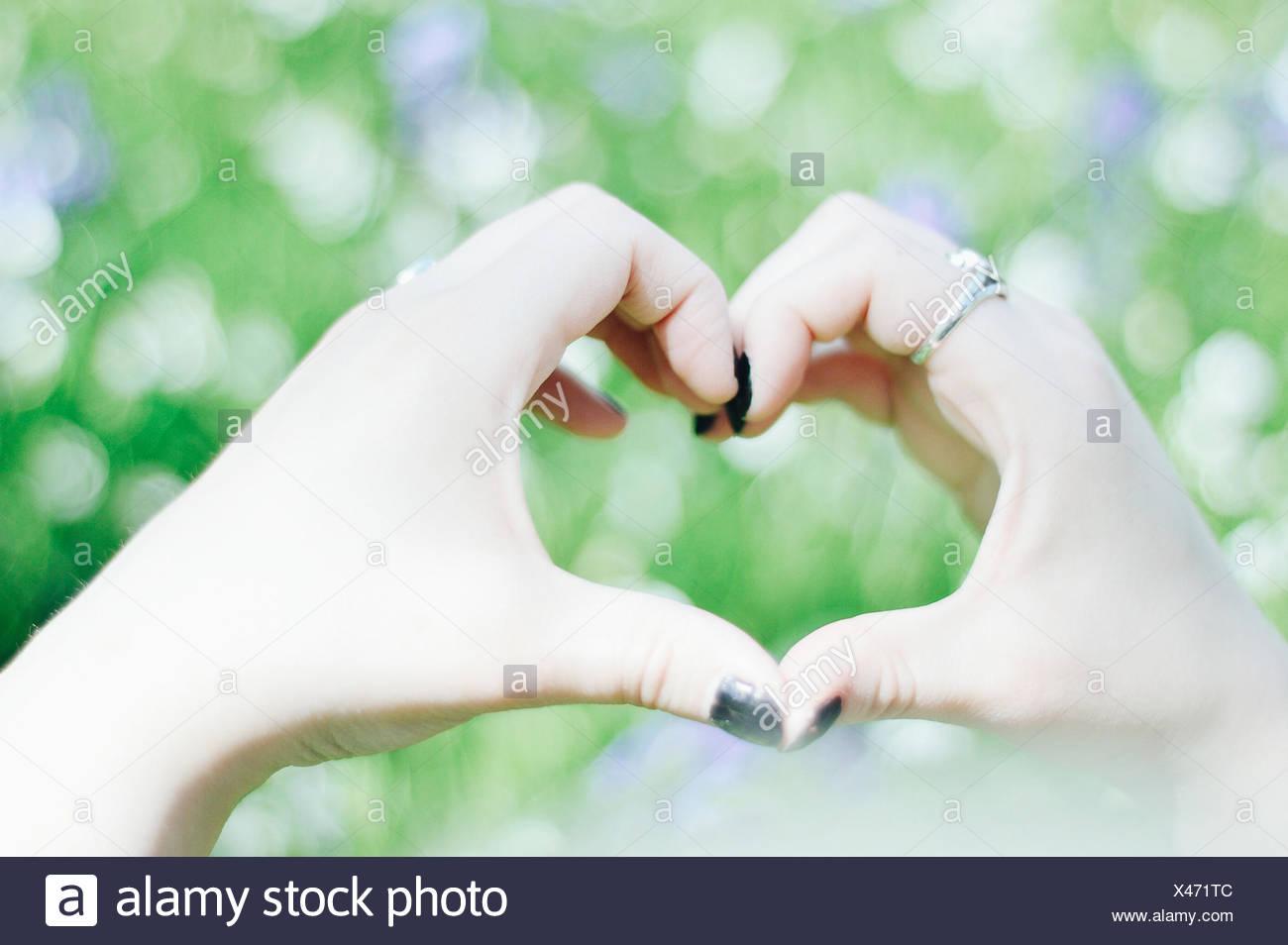 Frau macht Herzform mit Händen Stockbild