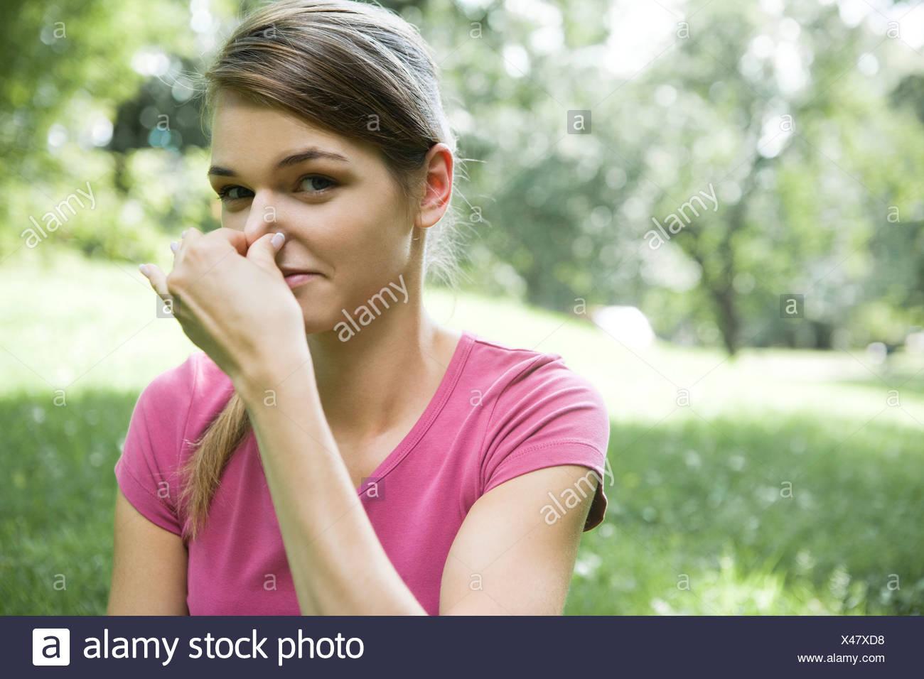 Nase der Frau-holding Stockbild