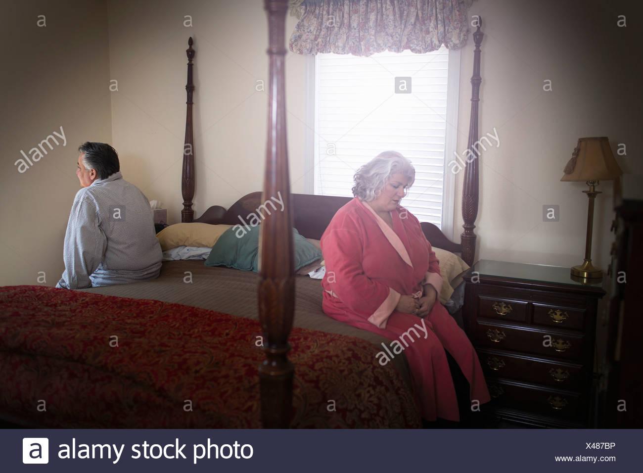 Älteres Paar auf gegenüberliegenden Seiten des Bettes sitzen Stockbild