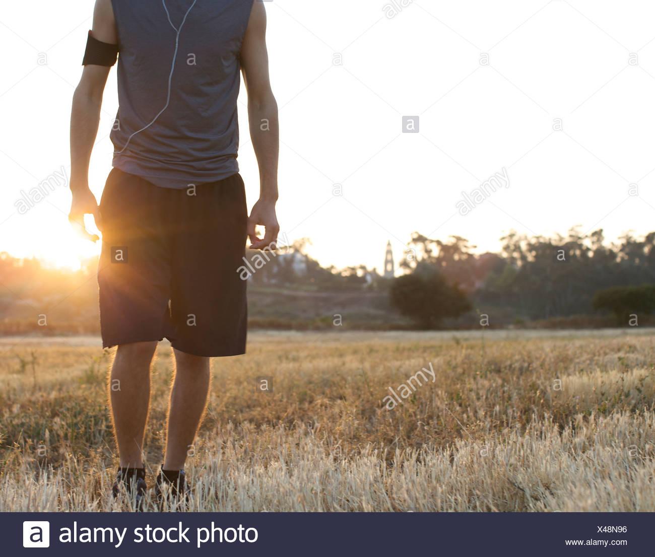 Männliche Läufer bleibt noch für ein Portrait auf einem offenen Feld mit Hintergrundbeleuchtung in San Diego, Kalifornien. Stockbild