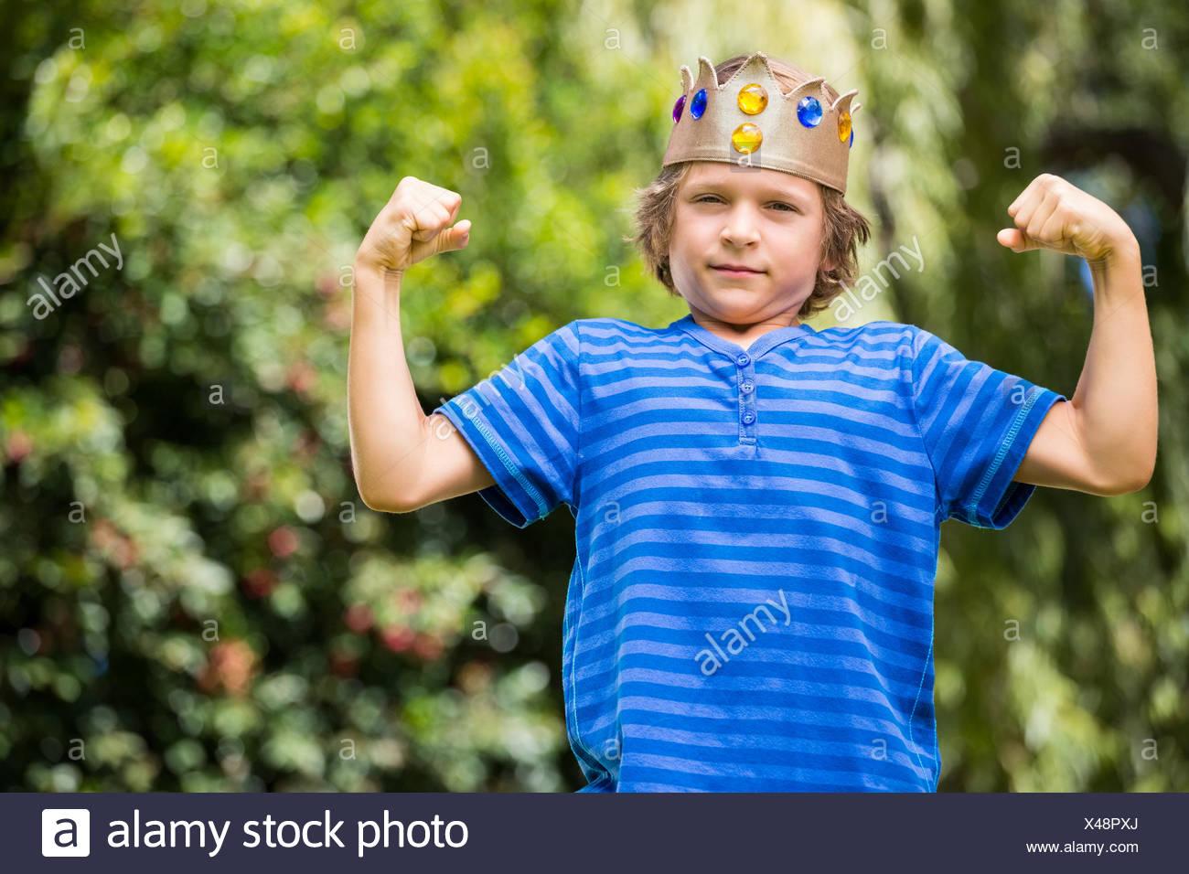 Süße Junge mit einer Krone seine Muskeln zeigen Stockbild