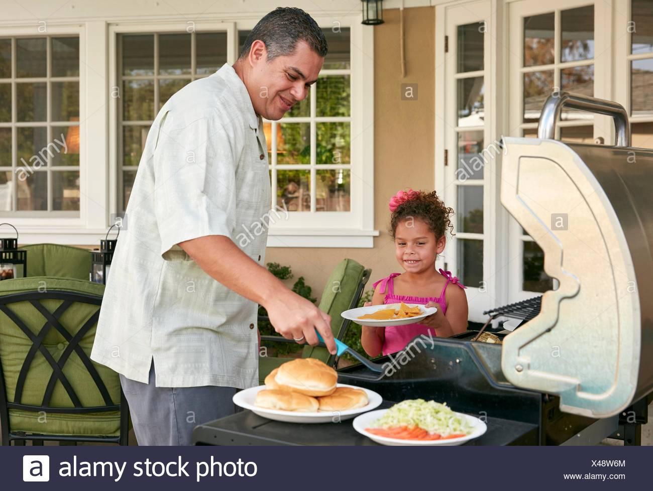 Vater und Tochter auf der Terrasse grillen Grill Essen Lächeln Stockbild