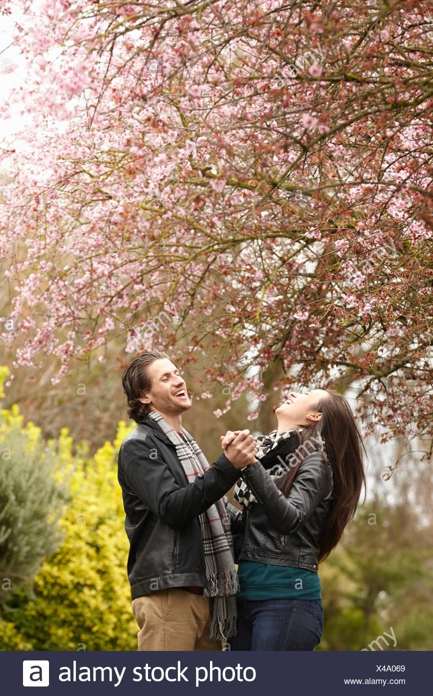 Junge Paare tanzen unter blühen im park Stockbild
