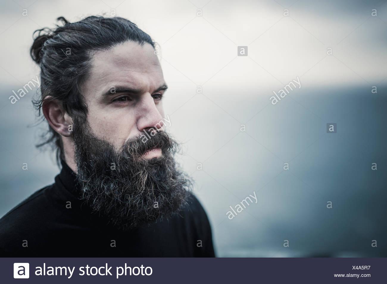 Ein Mann mit Vollbart und Schnurrbart und Schwarzes Haar verschrottet wieder aus dem Gesicht. Stockfoto