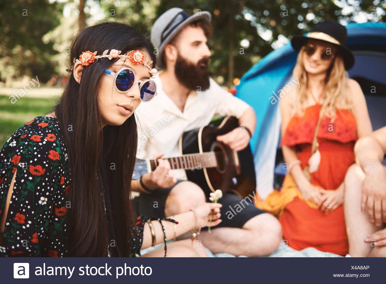 Junge boho Erwachsene spielen akustische Gitarre bei Festival Stockbild