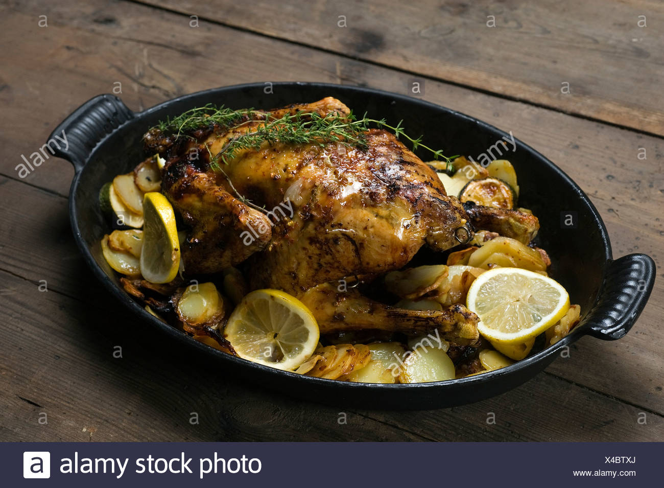 Zitronen-Hähnchen mit Thymian und Kartoffelgratin Stockbild