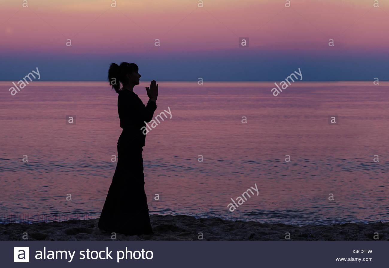 Silhouette einer Frau am Strand mit Hände im Gebet Position stehend Stockbild