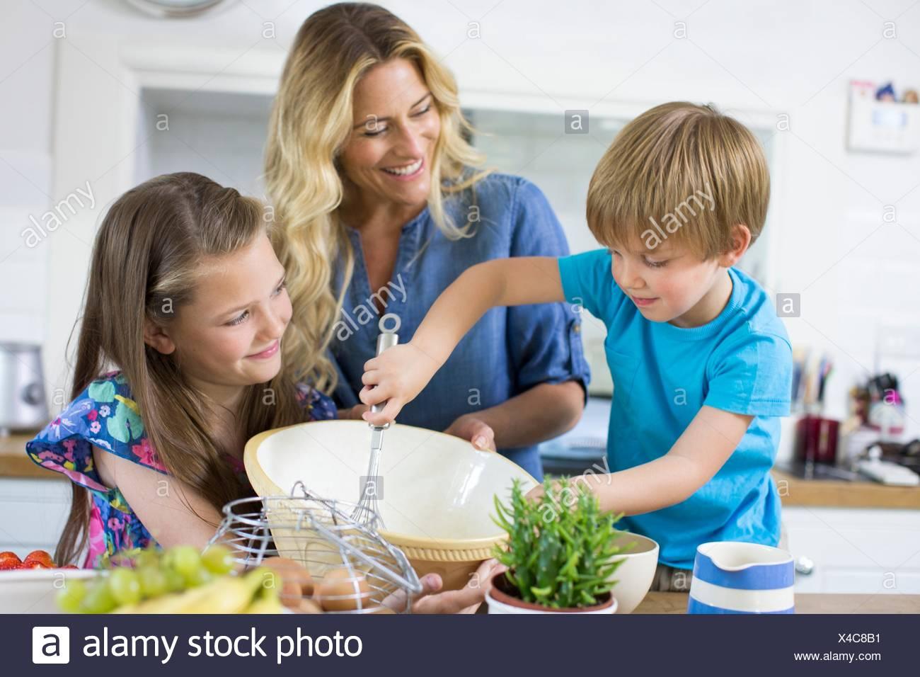 EIGENTUM FREIGEGEBEN. -MODELL VERÖFFENTLICHT. Mutter und Sohn und Tochter in der Küche. Stockbild