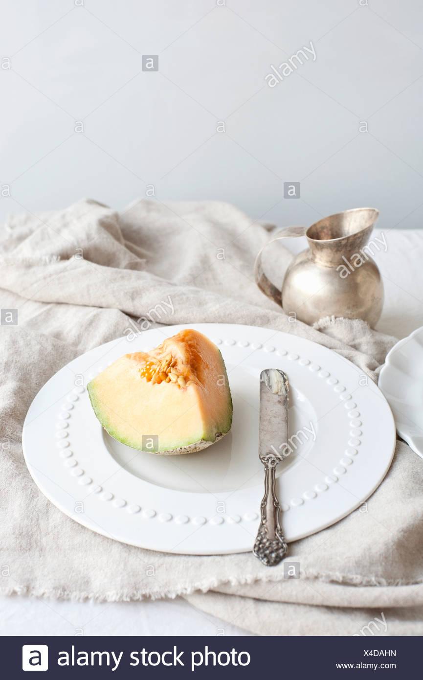 Teller mit Melone mit Buttermesser Stockbild