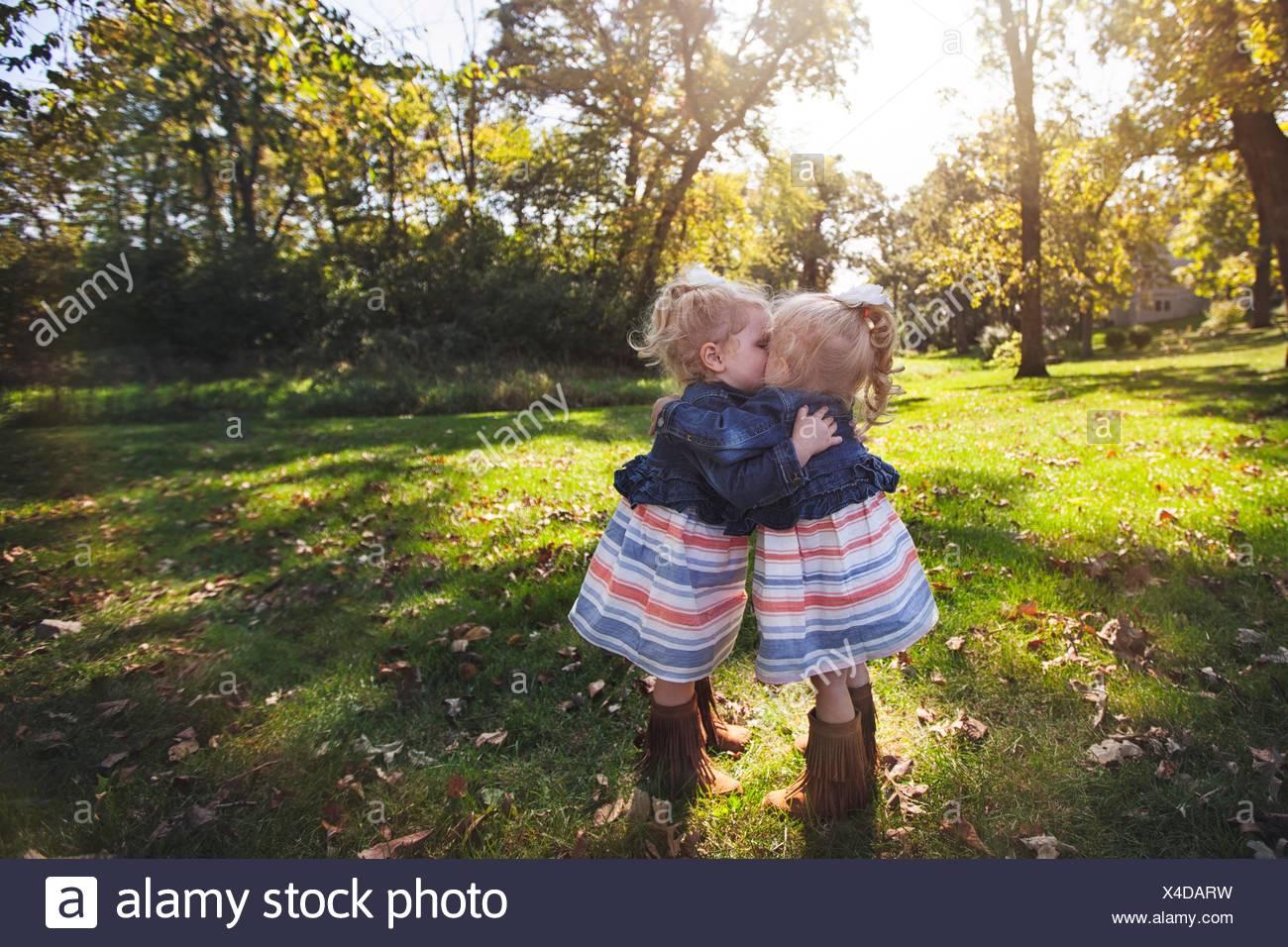 Zwillingsmädchen tragen passende Kleider von Angesicht zu Angesicht umarmen und küssen Stockbild