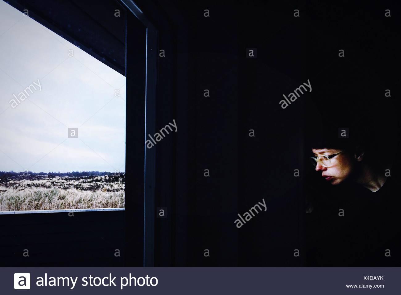 Nachdenkliche Frau trägt Brille sitzen zu Hause vor Fenster Stockbild