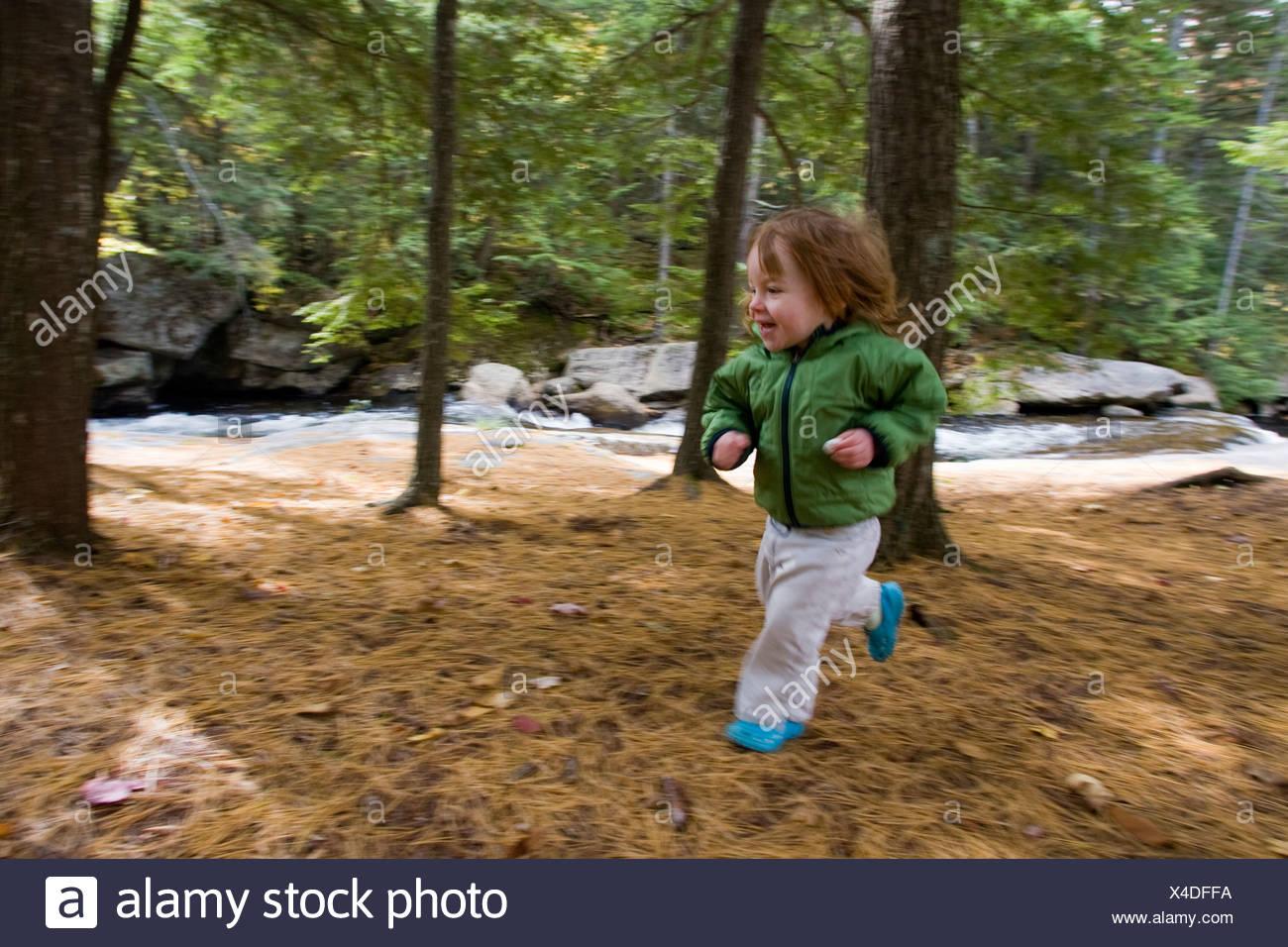 Ein junges Mädchen läuft durch den Wald. Stockbild