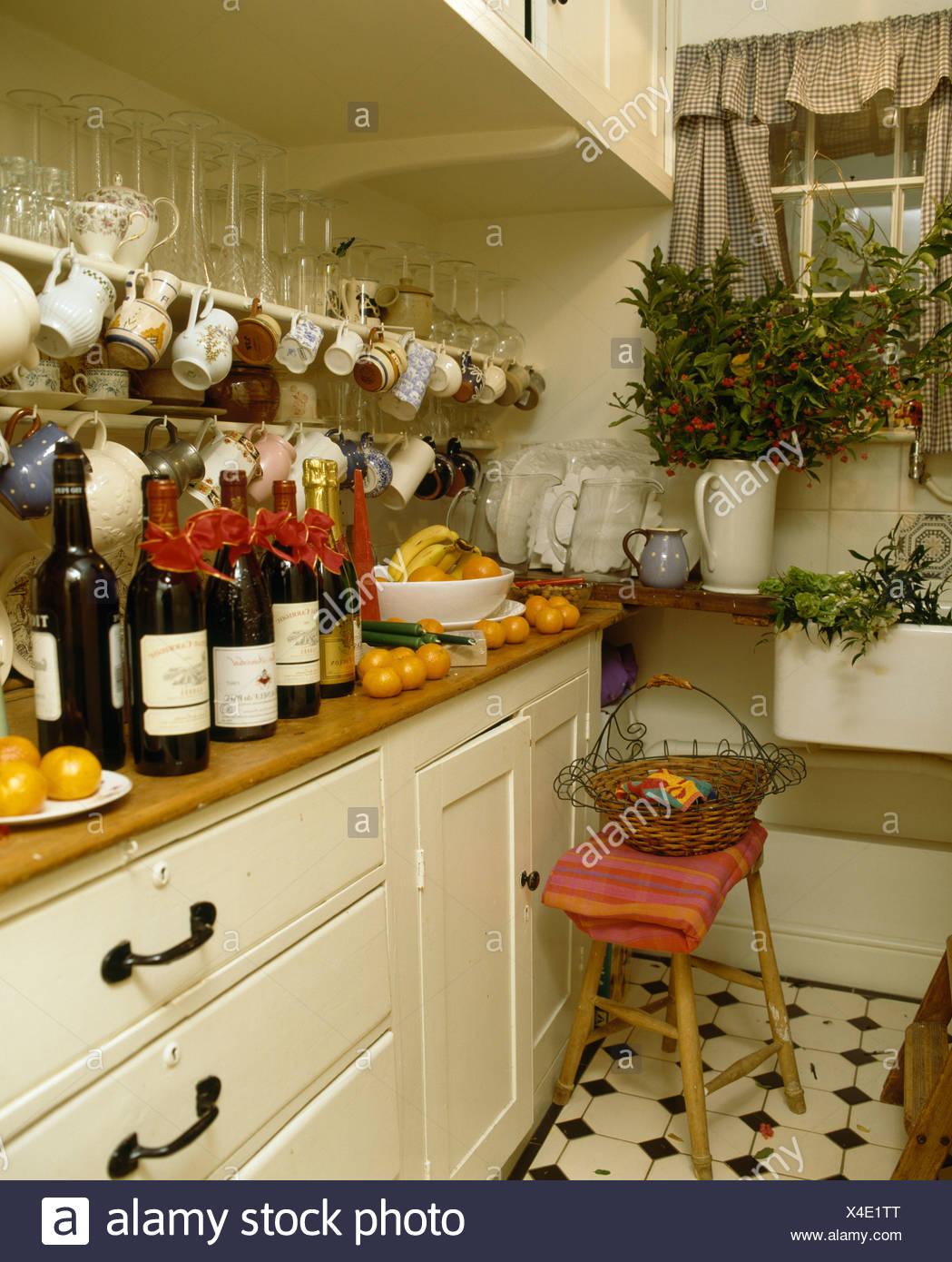 Flaschen Wein auf Arbeitsplatte unter Tassen und Kannen in Regalen ...
