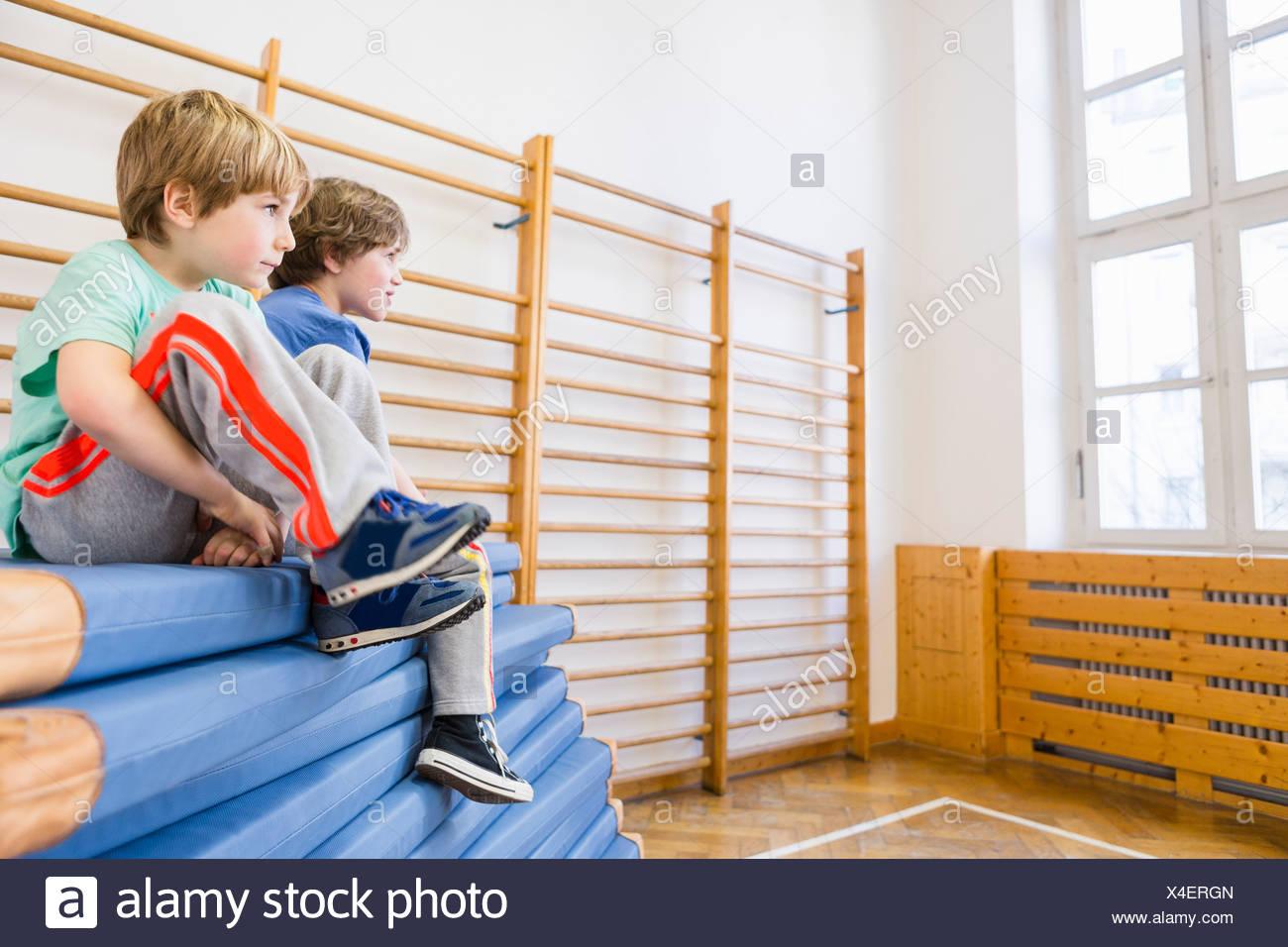 Jungen sitzen auf Haufen von blauen Trainingsmatten Stockbild