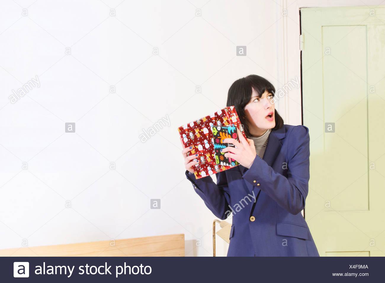Frau schütteln Weihnachtsgeschenk Stockfoto, Bild: 278161418 - Alamy