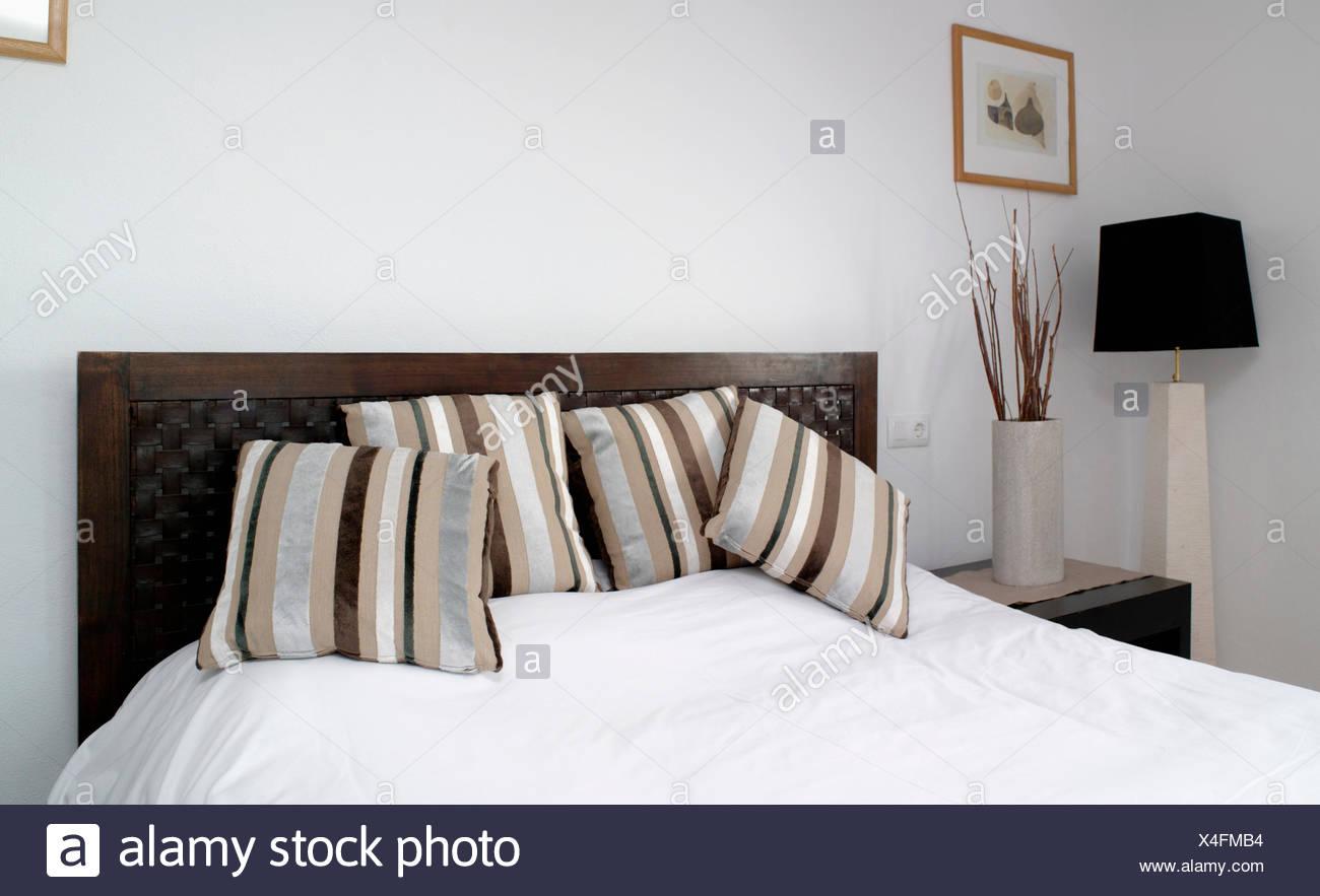 Grau + Beige gestreiften Samtkissen auf dem Bett mit weißen ...