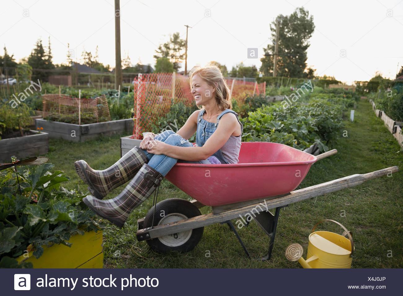 Lächelnde Frau karierte Gummistiefel sitzen Schubkarre Garten Stockbild