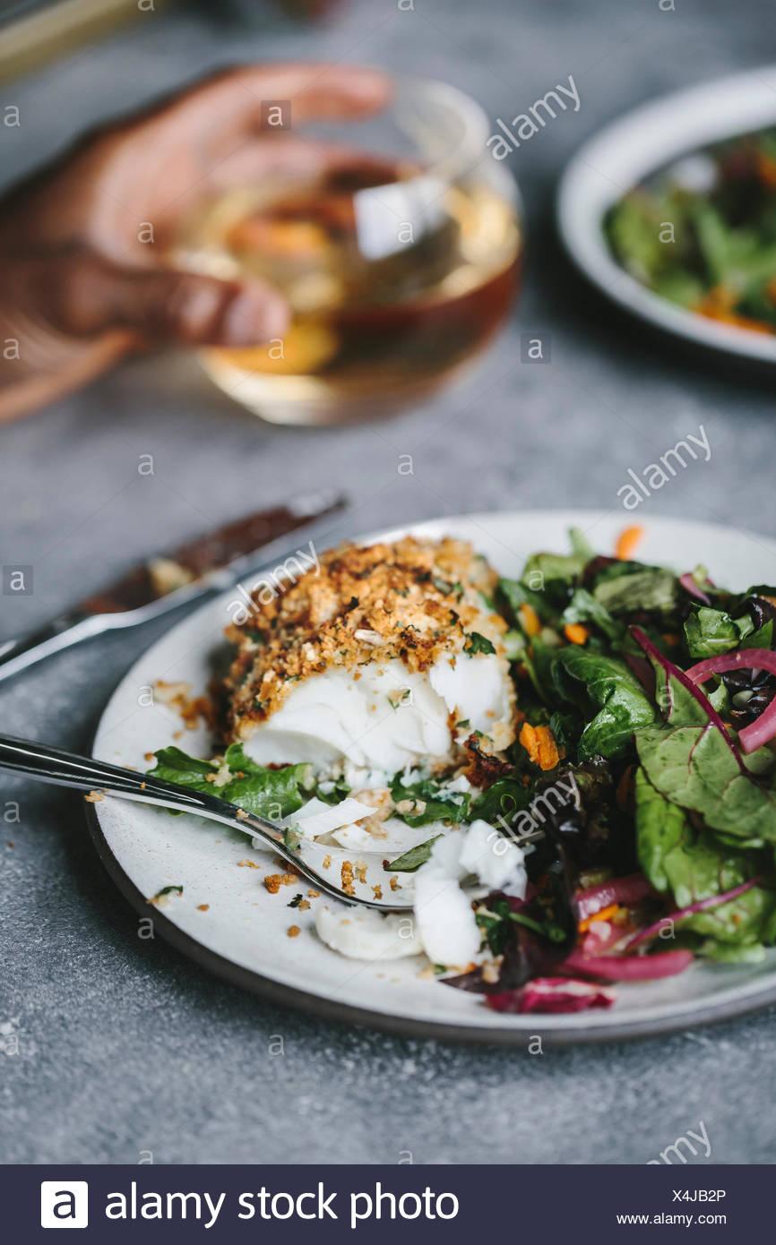 Ein halb gegessen gebratene Fisch zusammen mit etwas Salat wird von der Seite fotografiert. Stockbild
