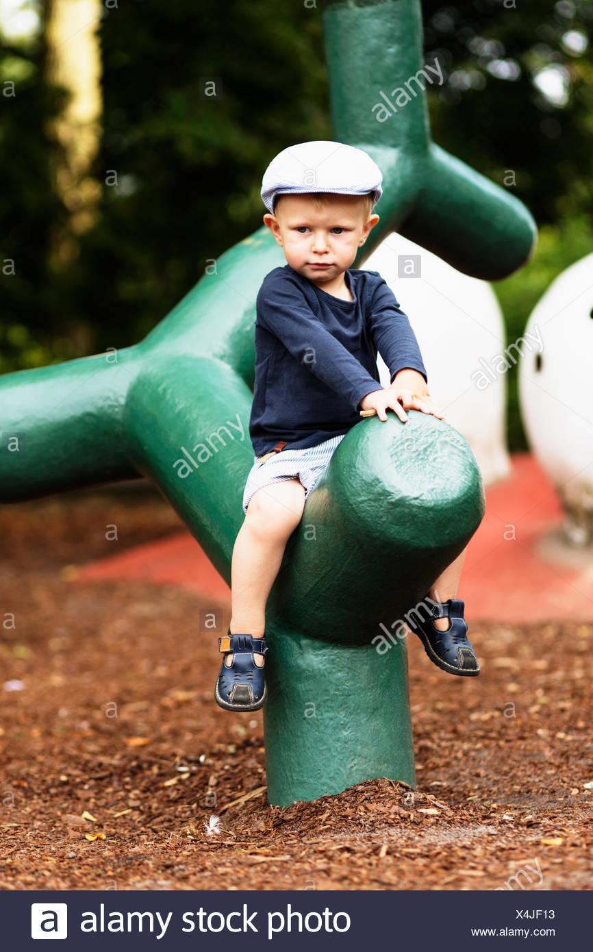 Gesamte Länge der Junge sitzt auf grüne Struktur auf Spielplatz Stockbild
