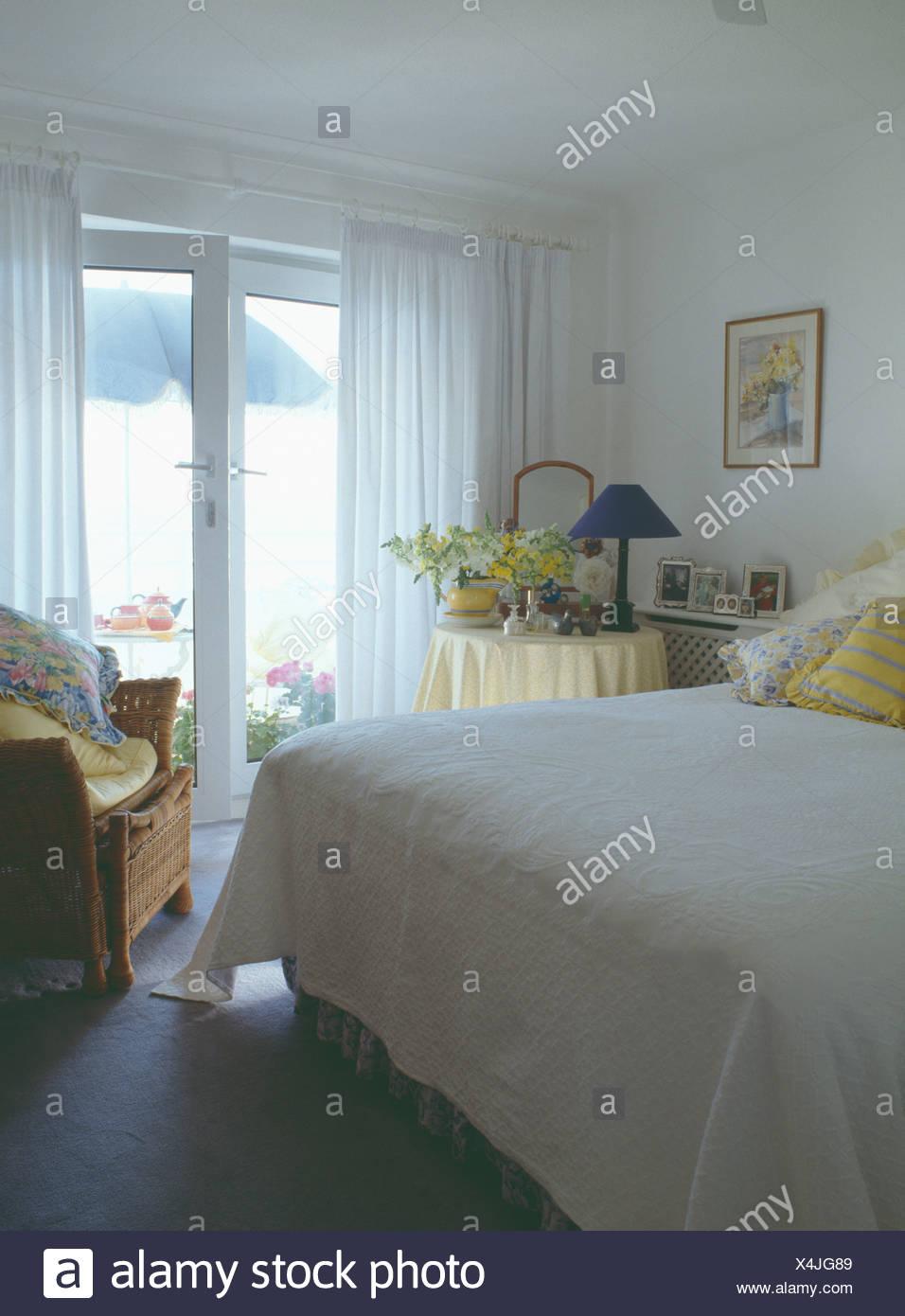 Meer Schlafzimmer mit weißen Quilt auf Bett und weiße Gardinen an