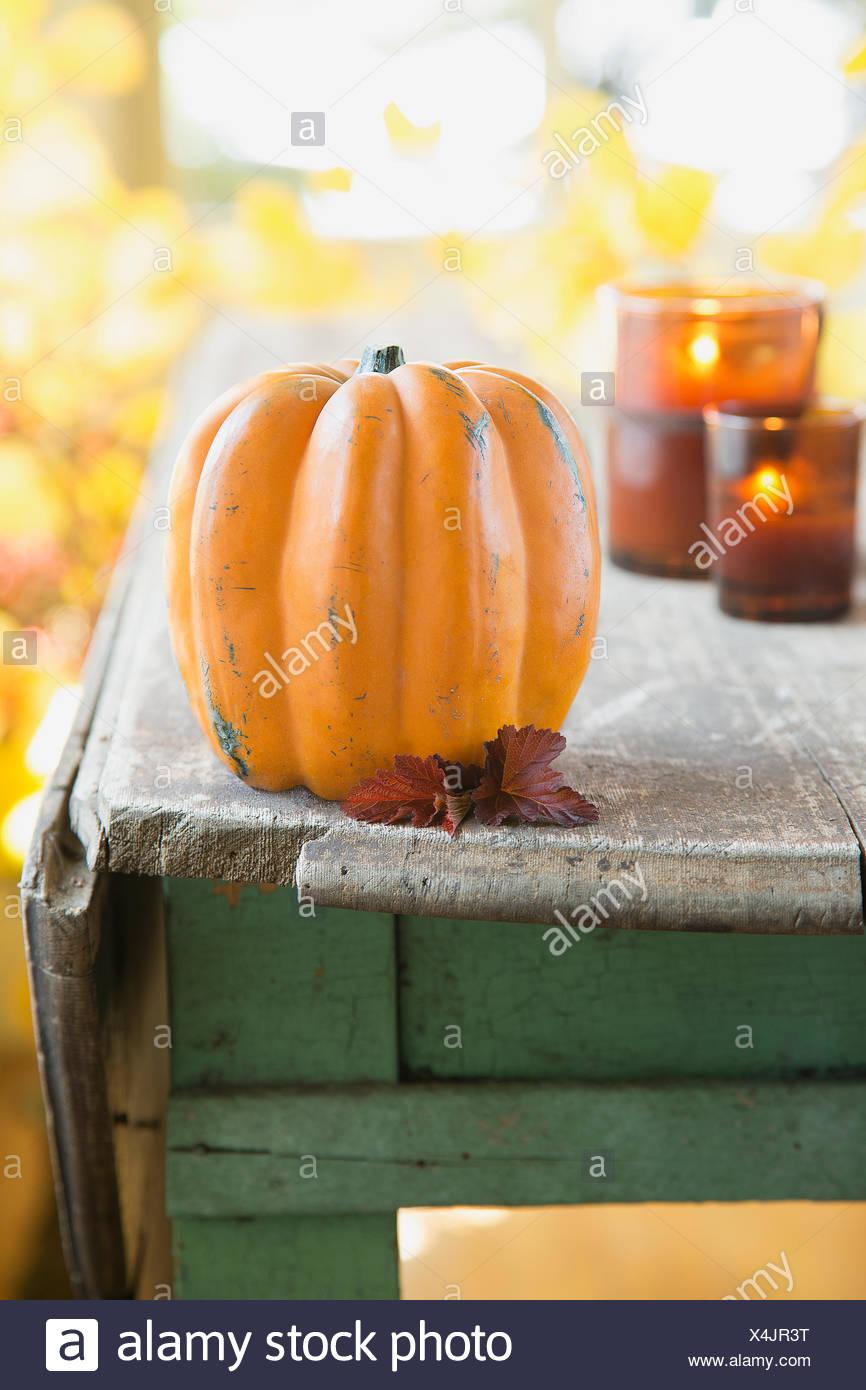Kürbis-Dekoration mit Kerzen auf rustikalen Holztisch Stockbild