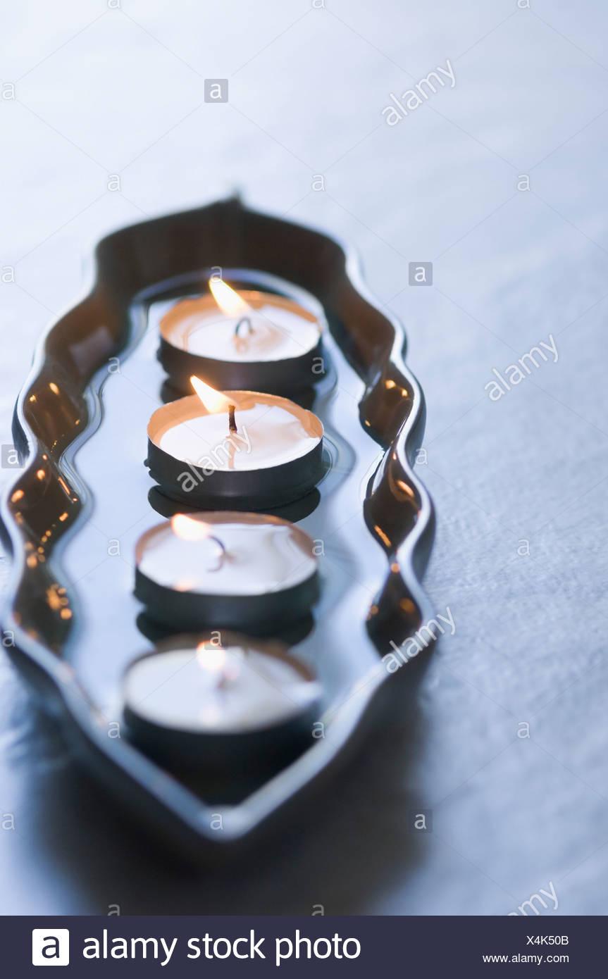 Nahaufnahme von vier Aromatherapie Kerzen brennen in einer Schale Stockbild