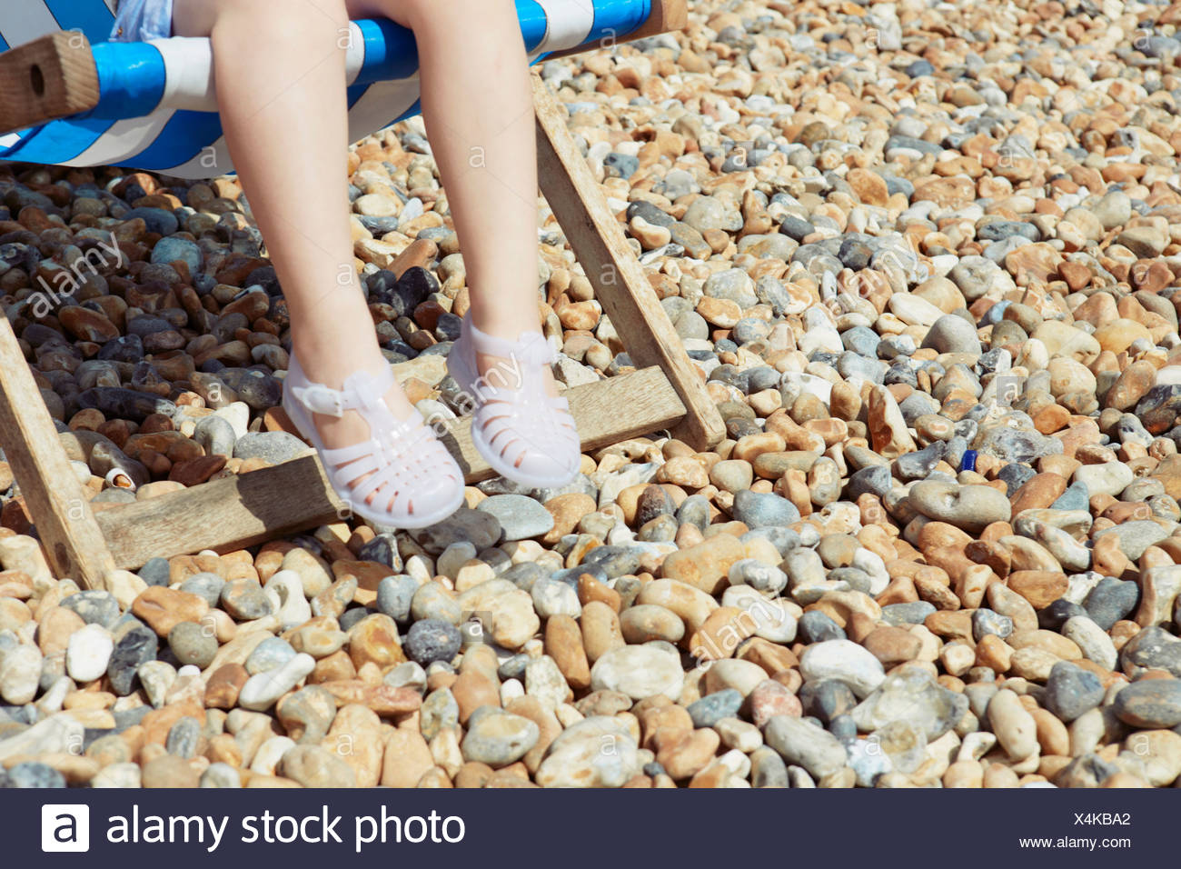 Kind mit Kunststoff-Sandalen auf Strand Liegestuhl Stockbild