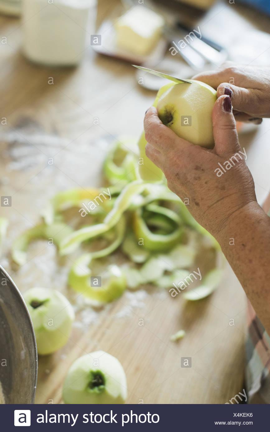 Eine Frau, einen dunkelhäutigen Apfel schälen. Stockbild