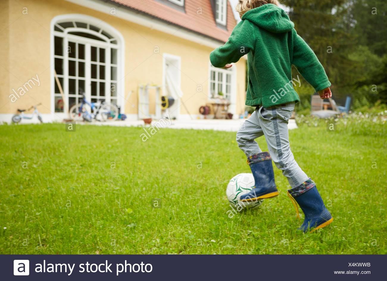 Rückansicht des jungen tragen Gummistiefel im Garten Fußball spielen Stockbild
