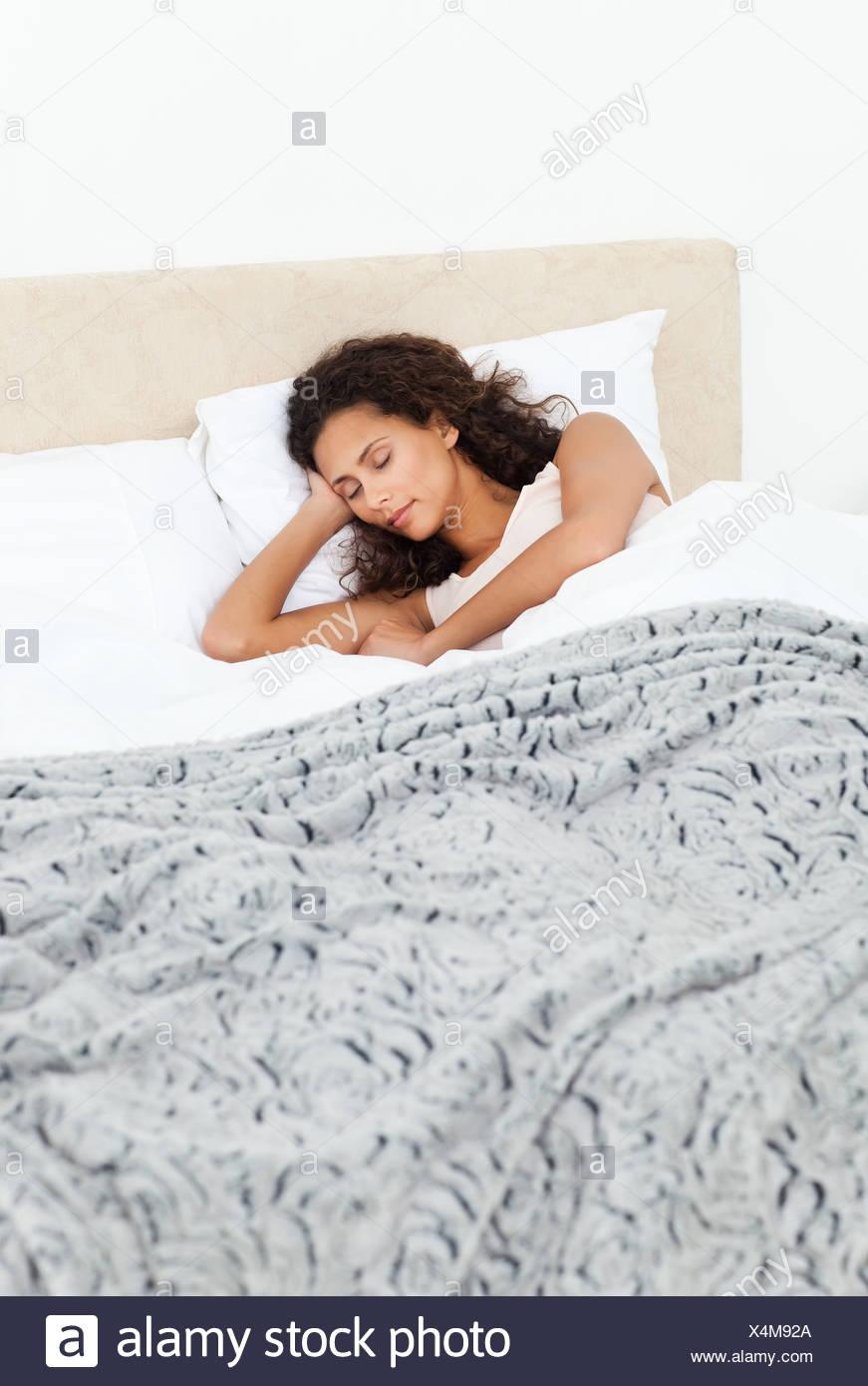 Schöne Frau friedlich schlafend auf ihrem Bett in den Morgen Stockbild