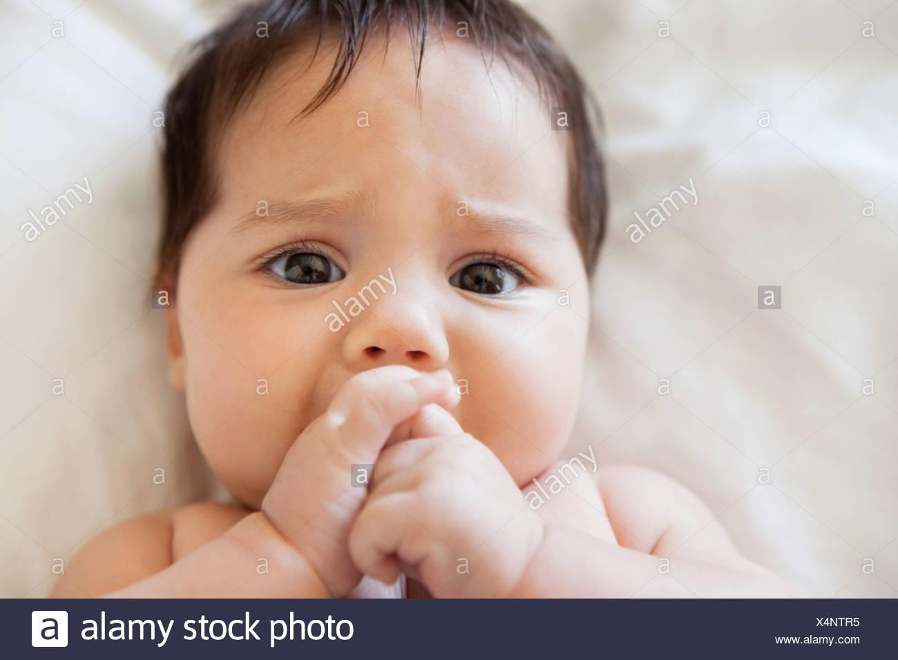 Pingelig Babymädchen saugen ihre Daumen Stockbild
