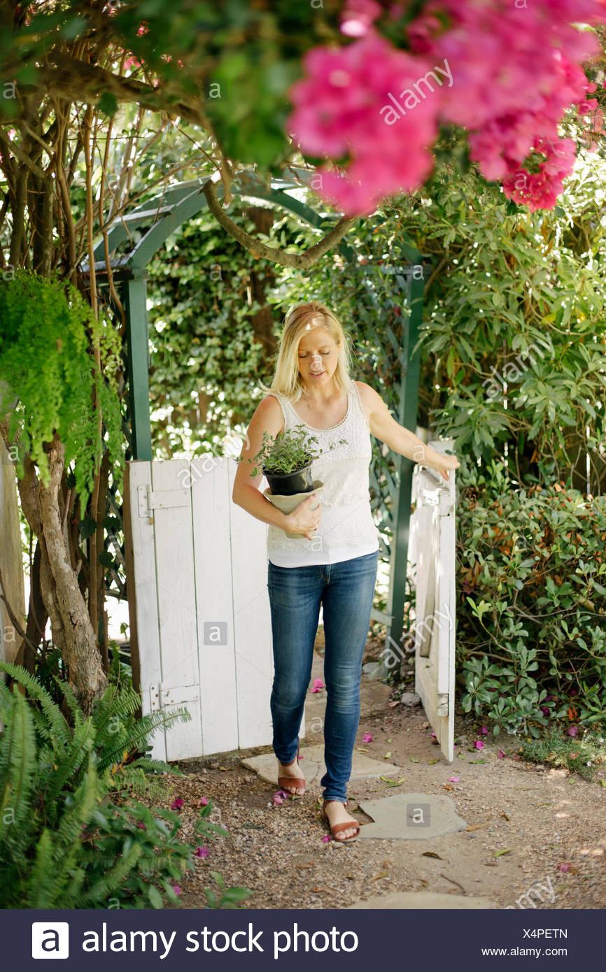 Blonde Frau in einem Garten durch ein weißes Holztor mit einem Blumentopf. Stockbild