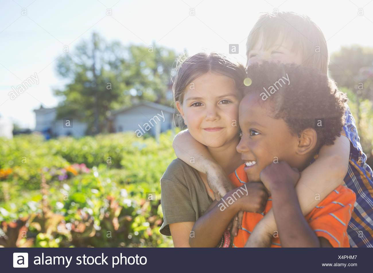 Porträt der niedliche Mädchen mit Freunden im Gemeinschaftsgarten Stockbild